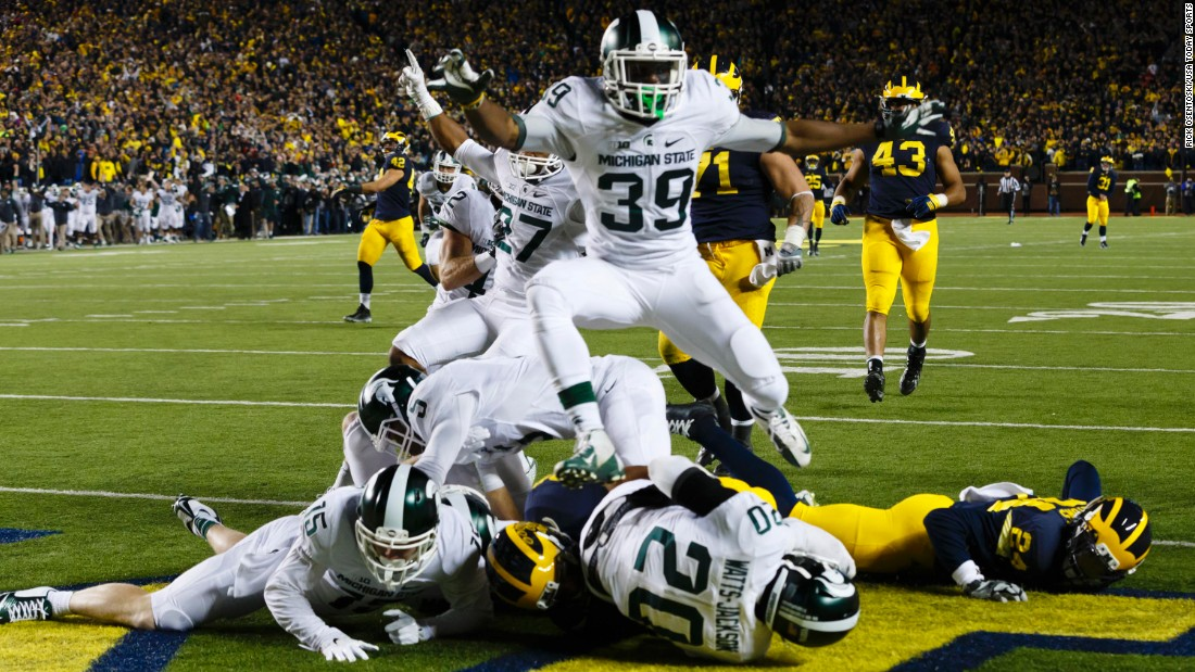 "Michigan State players crash into the end zone after Jalen Watts-Jackson <a href=""http://bleacherreport.com/articles/2580146-michigan-state-wins-on-walk-off-td-after-michigan-punter-fumbles-on-final-play"" target=""_blank"">scored an improbable touchdown</a> to defeat Michigan on Saturday, October 17. Michigan looked to have the game in hand until fumbling on a punt play with 10 seconds left. Watts-Jackson returned the ball for a 27-23 victory."