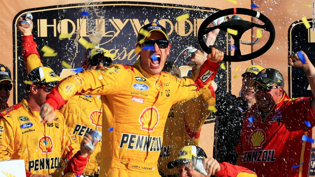 NASCAR driver Joey Logano celebrates with his crew after winning the Sprint Cup race at Kansas Speedway on Sunday, October 18.