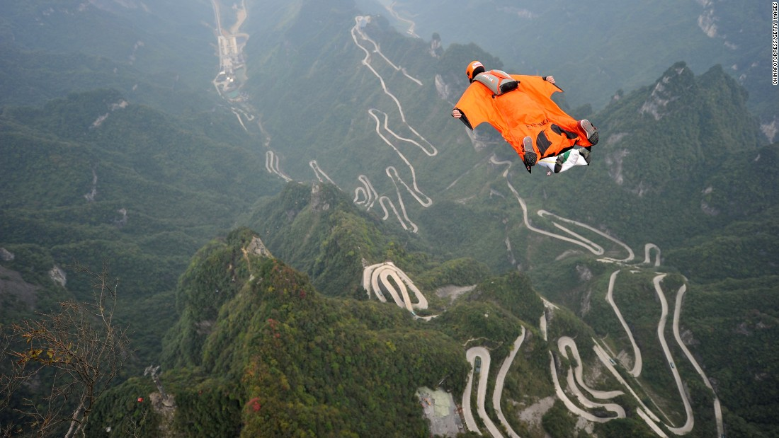 A person wears a wingsuit while flying above China's Tianmen Mountain on Tuesday, October 13.