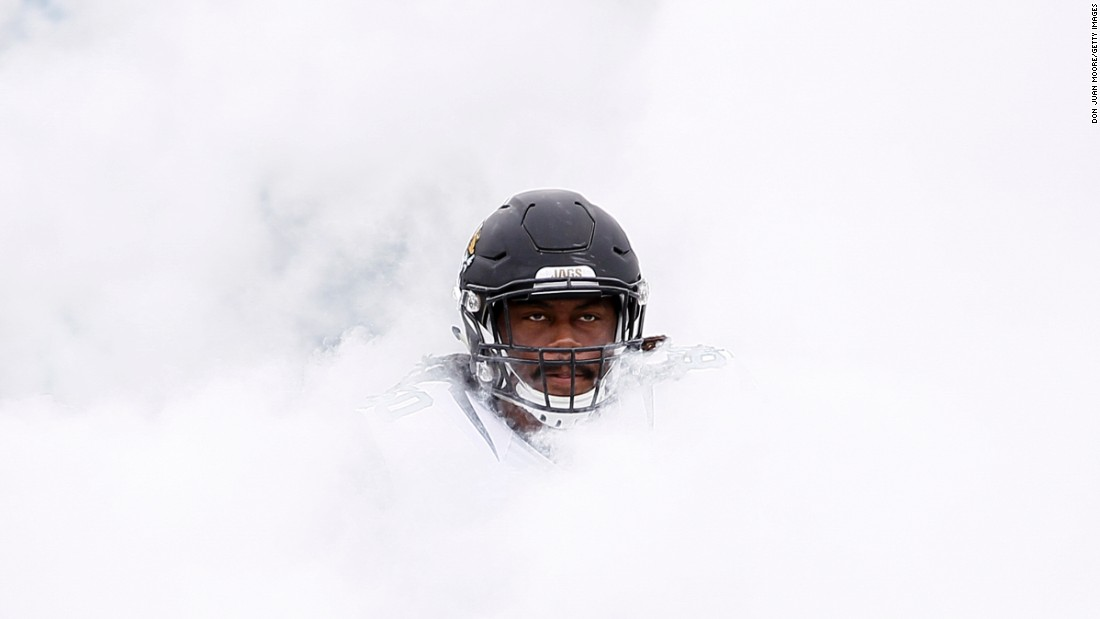 A.J. Cann, an offensive lineman for the NFL's Jacksonville Jaguars, emerges from a cloud of smoke before playing a home game against Houston on Sunday, October 18.