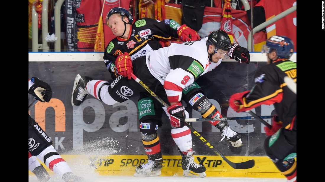 Dusseldorfer's Daniel Kreutzer is crunched by Kolnar Haie's Shawn Lalonde during a hockey game in Dusseldorf, Germany, on Sunday, October 18.