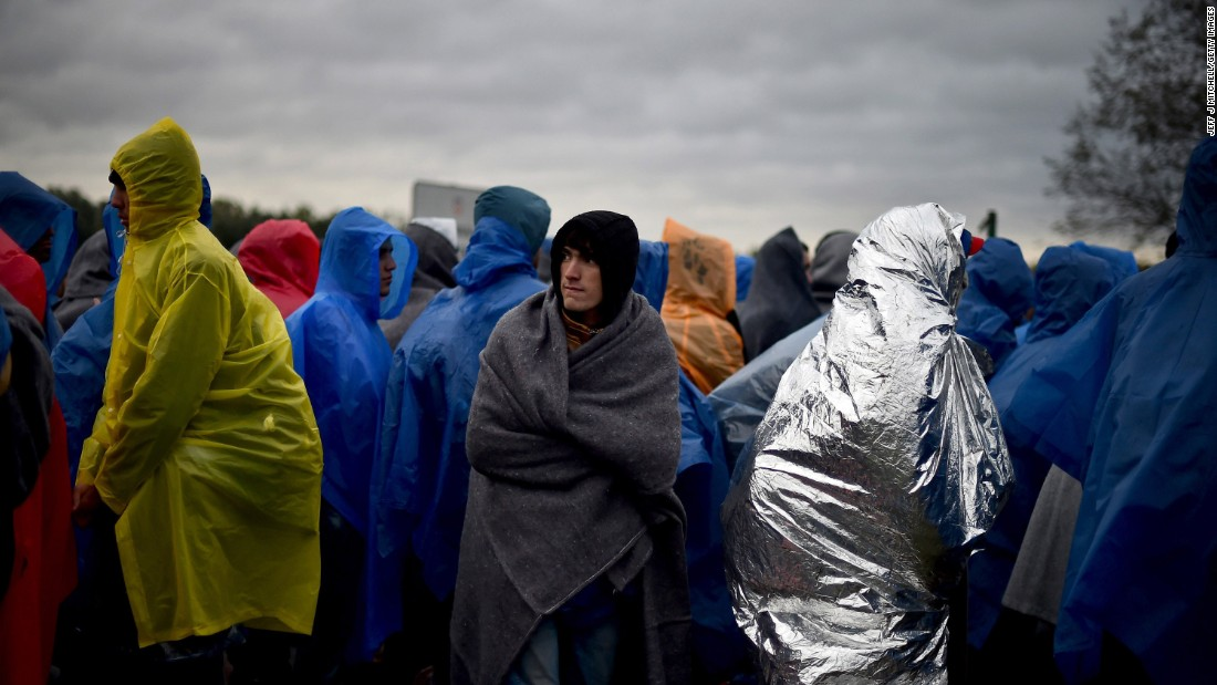 "Migrants waited in the rain at the Trnovec border crossing in Croatia on Monday. Amnesty International described the conditions there as ""dire."""
