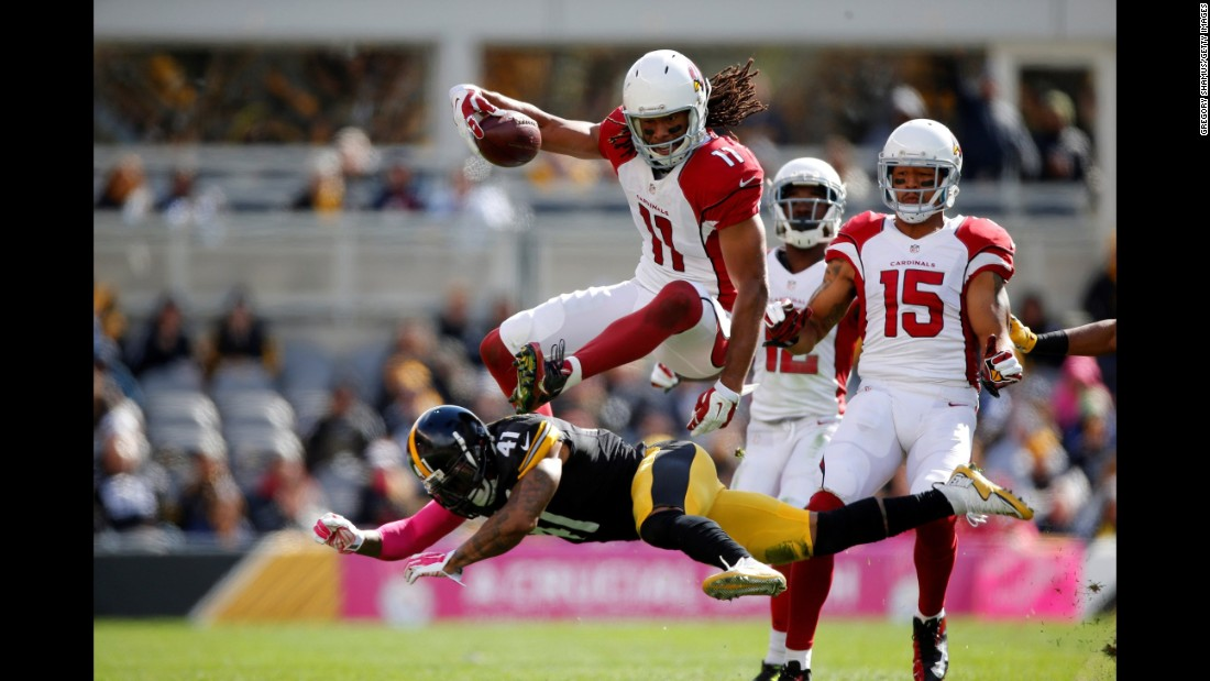 Arizona wide receiver Larry Fitzgerald jumps over a defender during an NFL game in Pittsburgh on Sunday, October 18.