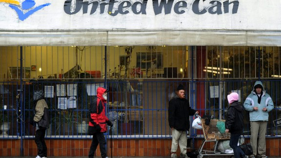 It's located in the Downtown Eastside area of Vancouver, a neighborhood known for its poverty and deprivation. Pictured, a group of homeless and poor people seek shelter from the rain outside a store.