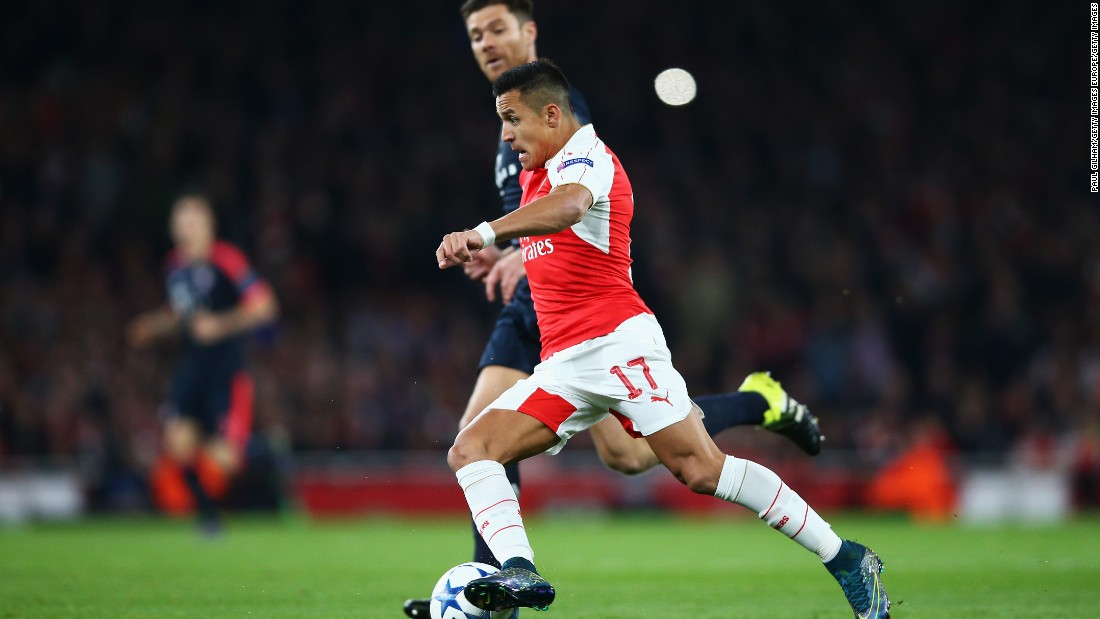 Alexis Sanchez of Arsenal is chased by Xabi Alonso of Bayern Munich during the UEFA Champions League Group F match between Arsenal FC and FC Bayern Munchen at Emirates Stadium.