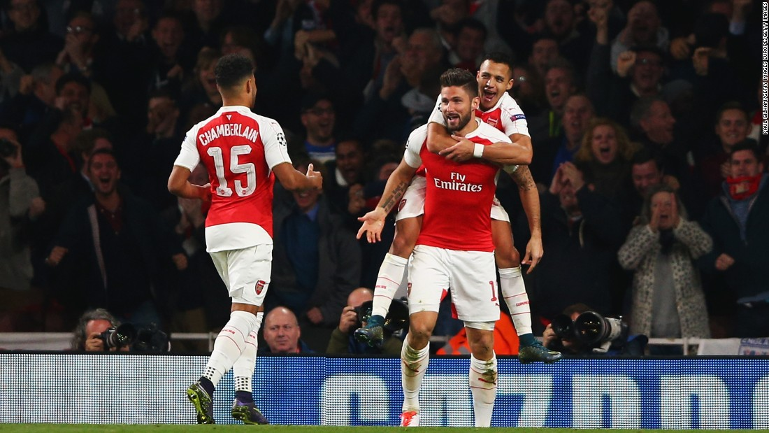 Olivier Giroud of Arsenal (C) celebrates with Alex Oxlade-Chamberlain (15) and Alexis Sanchez as he scores their first goal during the UEFA Champions League Group F match between Arsenal FC and FC Bayern Munchen at Emirates Stadium.