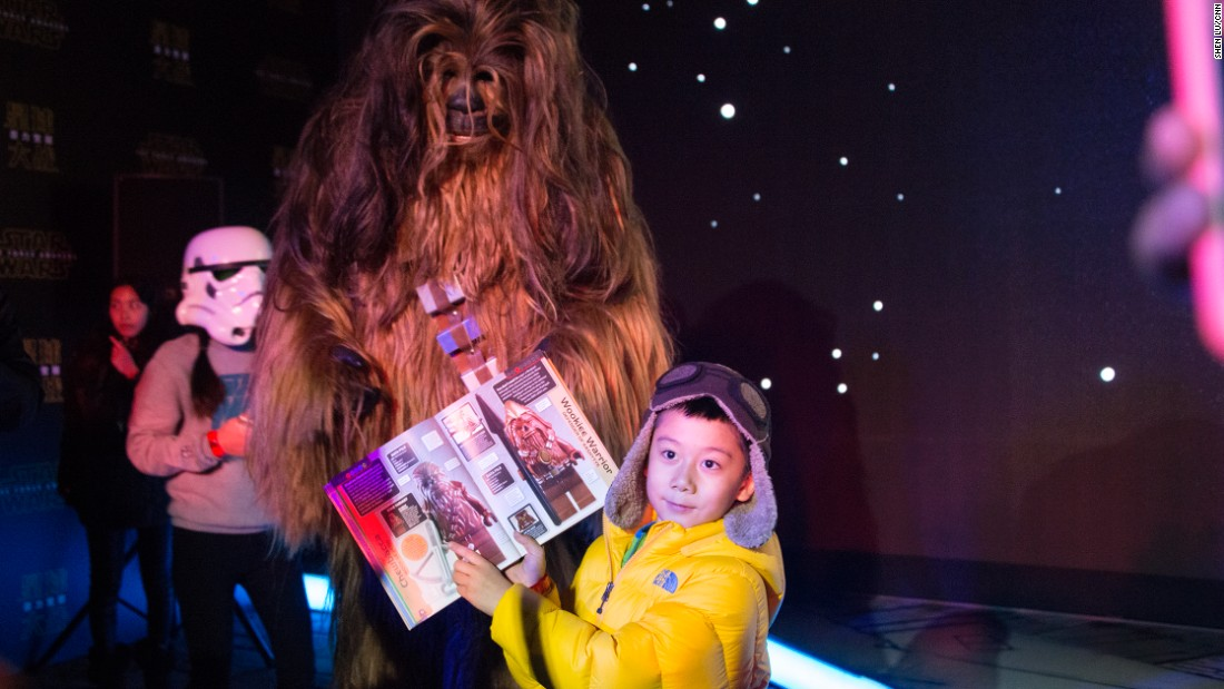 A young Chinese Star Wars fan excitedly poses next to a Wookie for a photo during the event.