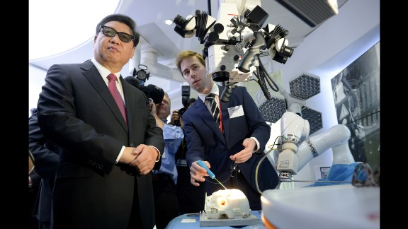 Xi wears 3-D glasses as he views robotic equipment October 21 at Imperial College London.