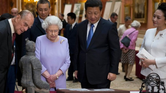 Prince Philip, Queen Elizabeth II, Xi and Peng view a display of Chinese items from the Royal Collection at Buckingham Palace.