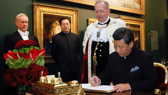 Xi signs the distinguished visitors book before a banquet at the Guildhall in London on Wednesday, October 21.