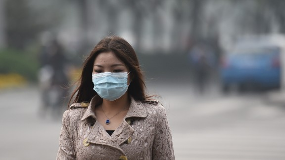 To go with China-environment-pollution-health-economy,FOCUS by Neil CONNOR This photo taken on October 20, 2014 shows a woman wearing a mask on a heavily polluted day in Beijing. The soaring, grimy chimneys of the coal-fired power station have belched the last of their choking fumes into Beijing's air, authorities say -- but experts doubt the plan will ease the capital's smog.  AFP PHOTO/Greg BAKER        (Photo credit should read GREG BAKER/AFP/Getty Images)