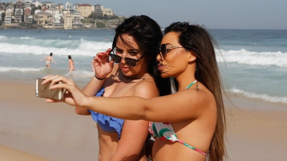 SYDNEY, AUSTRALIA - OCTOBER 31:  Friends take a selfie as they enjoy the warm weather down at Bondi Beach on October 31, 2014 in Sydney, Australia.  Australia is expecting much hotter temperatures than usual for the next three months.  (Photo by Daniel Munoz/Getty Images)