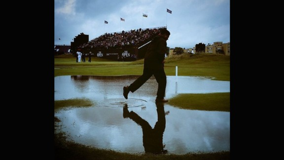 """CNN's Chris Murphy captured this shot at St. Andrews soon after the deluge. The gray skies and man skipping through the puddle illustrate just how quickly the rain fell and waterlogged the course. """"A tad wet at St Andrews on Friday. All adds to the fun, when you're sitting in the warm & toasty media center anyway,"""" he said."""