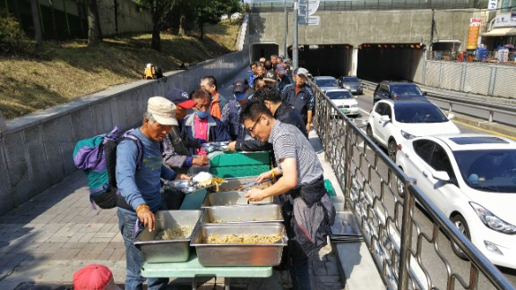 People line up to receive food from Pastor Choi Seong-Won's mobile soup kitchen.