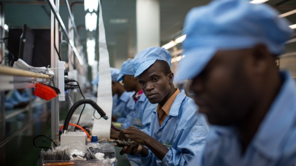 """In 2012, economic activity related to mobile phones and their life-cycle accounted for about 3.3 million jobs.   Pictured:  Employees work on mobile phones on the assembly line at the VMK (for """"Vumbuka"""", """"Wake up"""" in Kituba) factory in Brazzaville on July 20, 2015. The factory, run by Verone Mankou, produces the first mobile phones made in French speaking Africa."""