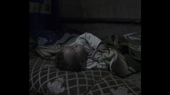 """Amir, 20 months old, was born a refugee. His mother believes he was traumatized in the womb. """"Amir has never spoken a single word,"""" she said. In the plastic tent where the family now lives in Zahle, Lebanon, Amir has no toys. But he plays with whatever he can find on the ground. """"He laughs a lot, even though he doesn't talk,"""" his mother said."""