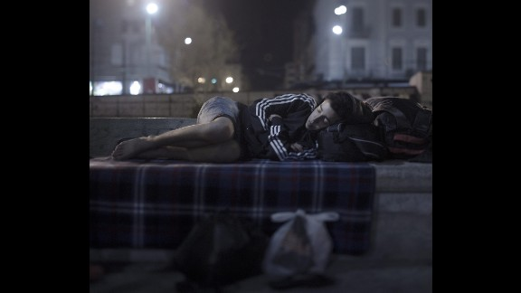 """Abdul Karim Addo, 17, sleeps in Omonoia Square in Athens, Greece. He has no money left. He bought a ferry ticket to Athens with his last euros. Now he spends the night where hundreds of refugees are arriving every day. He is able to borrow a telephone and call home to his mother in Syria, but he is not able to tell her how bad things are. """"She cries and is scared for my sake, and I don't want to worry her more,"""" he said. He unfolds his blanket in the middle of the square and curls up in the fetal position. """"I dream of two things: to sleep in a bed again and to hug my younger sister."""""""