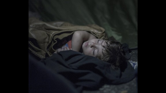 Mahdi, 1, sleeps deeply despite hundreds of refugees climbing around him in Horgos. They were protesting against not being able to travel further through Hungary. On the other side of the border, hundreds of police were standing.