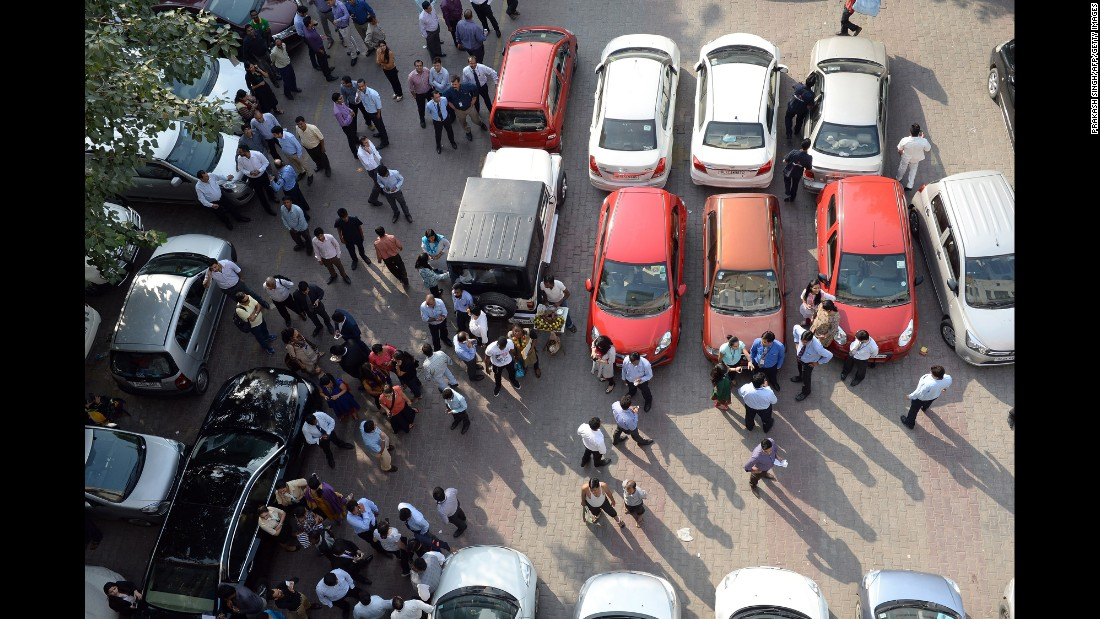 People stand in an open area in a parking lot in New Delhi after the quake.