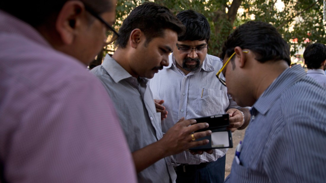 People in New Delhi look for news of the earthquake on their phones.