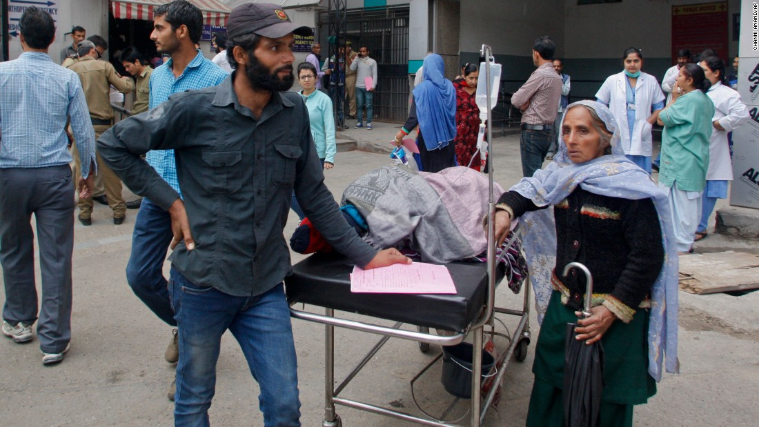 People wait after being shifted outdoors at the government medical college hospital in Jammu, India.
