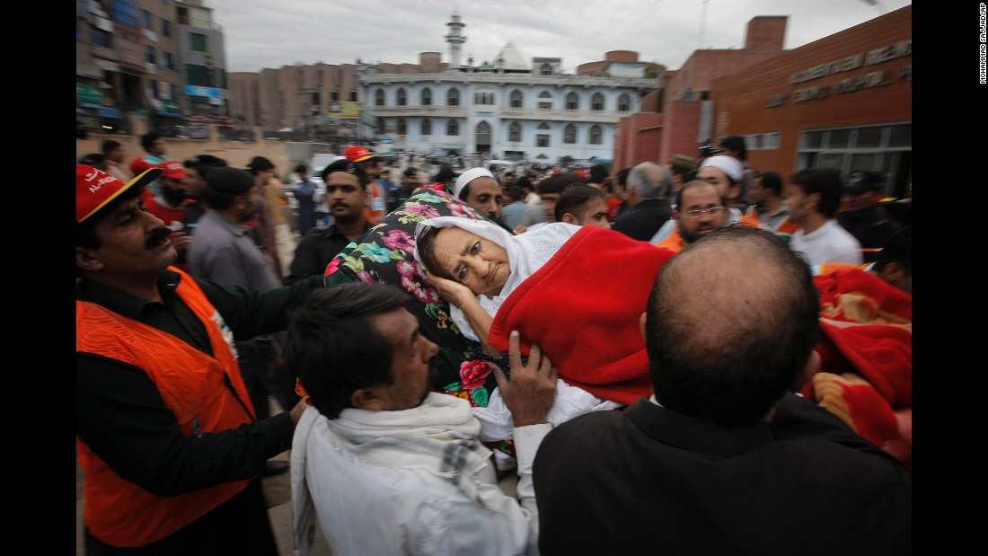 People rush an injured woman to a local hospital in Peshawar on October 26.
