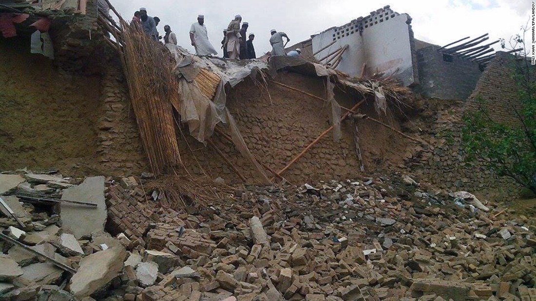 People look at collapsed houses in the Khyber Agency region of Pakistan.