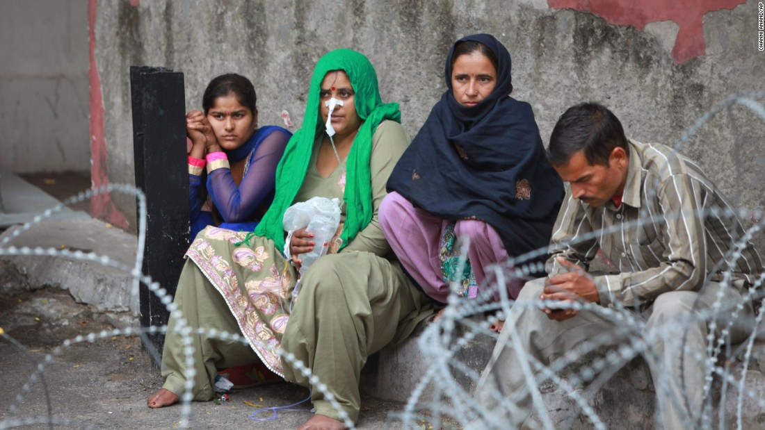 Patients sit outside the government medical college hospital after a strong tremor was felt in Jammu, India.