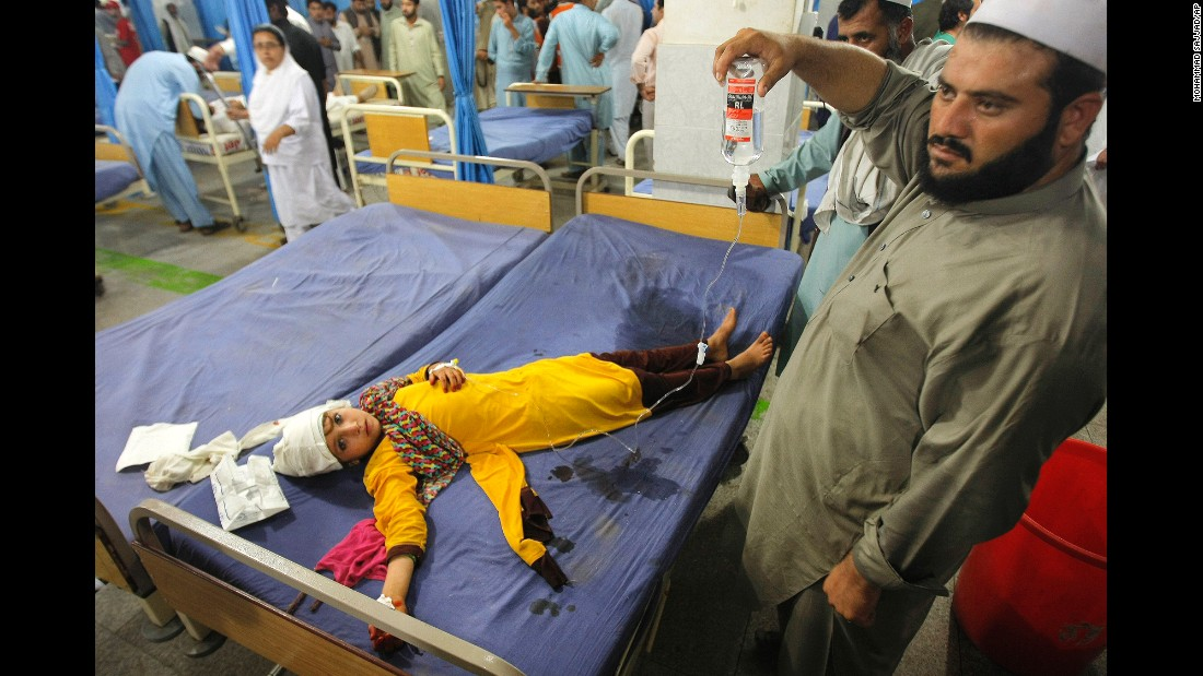 A injured girl lies on a bed at a hospital in Peshawar.