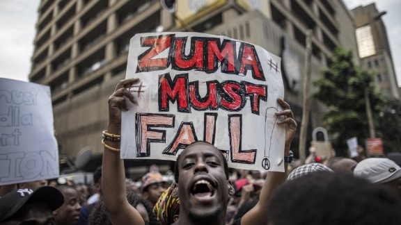 """A student holds a placard reading 'A placard with """"Zuma must fall"""" outside the Luthuli House, the ANC headquarters, on October 22, 2015, in Johannesburg, during a demonstration of thousands of students against university fee hikes."""