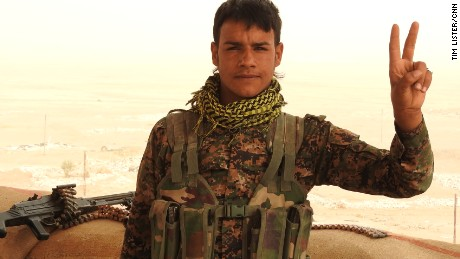 A Kurdish YPG fighter poses for a photograph on the frontline in northern Syria