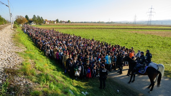 Police escort migrants toward a refugee center after crossing the Croatian-Slovenian border in 2015.