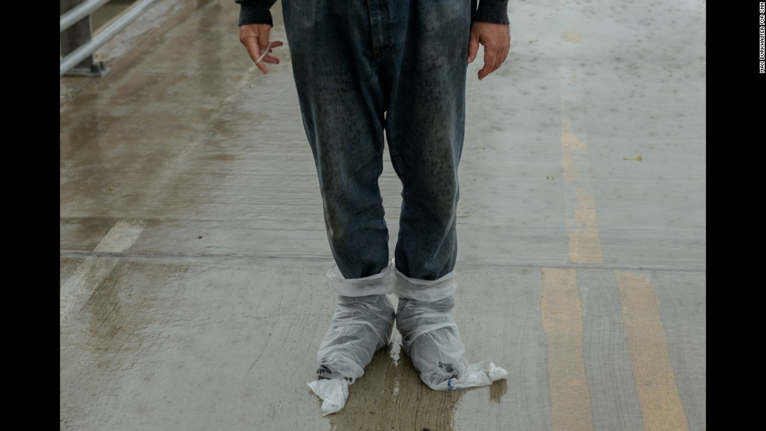 "A man walks alone near the Harris County Jail with his feet encased in plastic bags. ""I just thought it was a really good representation of this storm that was about to come,"" Burkhalter said."
