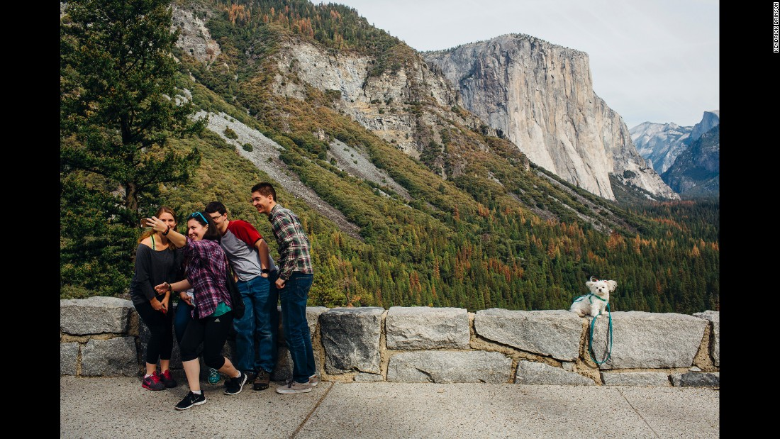 Visitors gather for a selfie as a nearby dog is photographed by its owner at the Tunnel View scenic overlook in Yosemite National Park on Saturday, October 24.