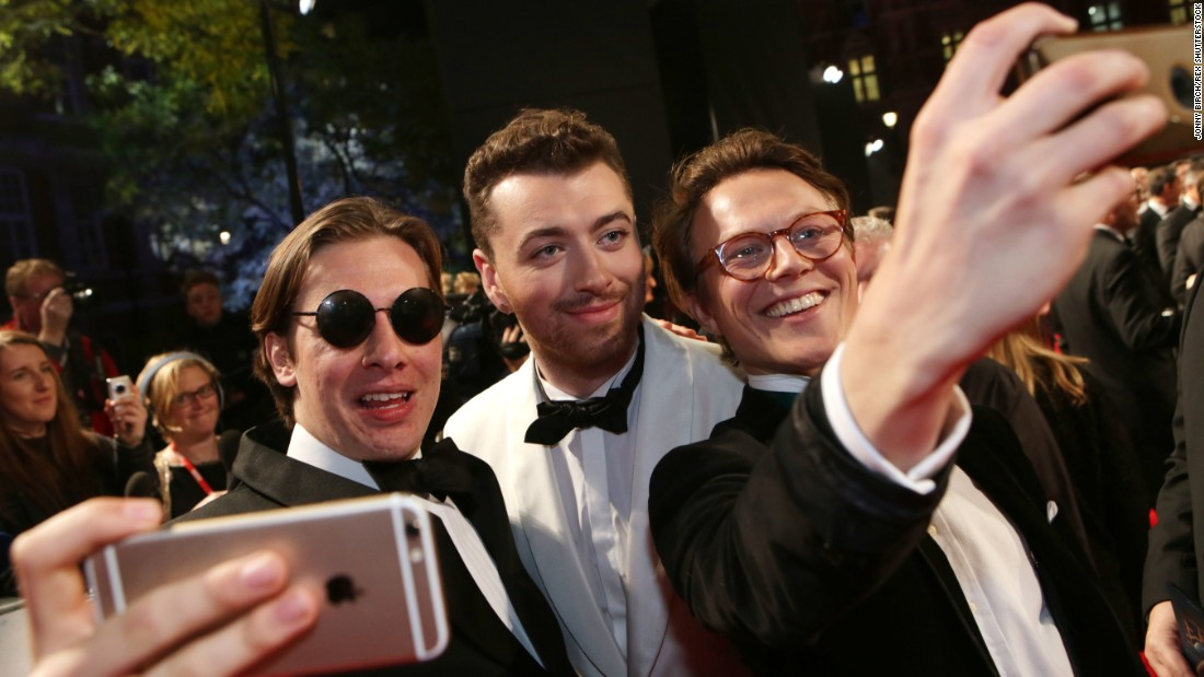 "Singer Sam Smith, center, takes a selfie at the James Bond ""Spectre"" premiere in London on Monday, October 26. Smith recorded the film's theme song, ""Writing's on the Wall."""