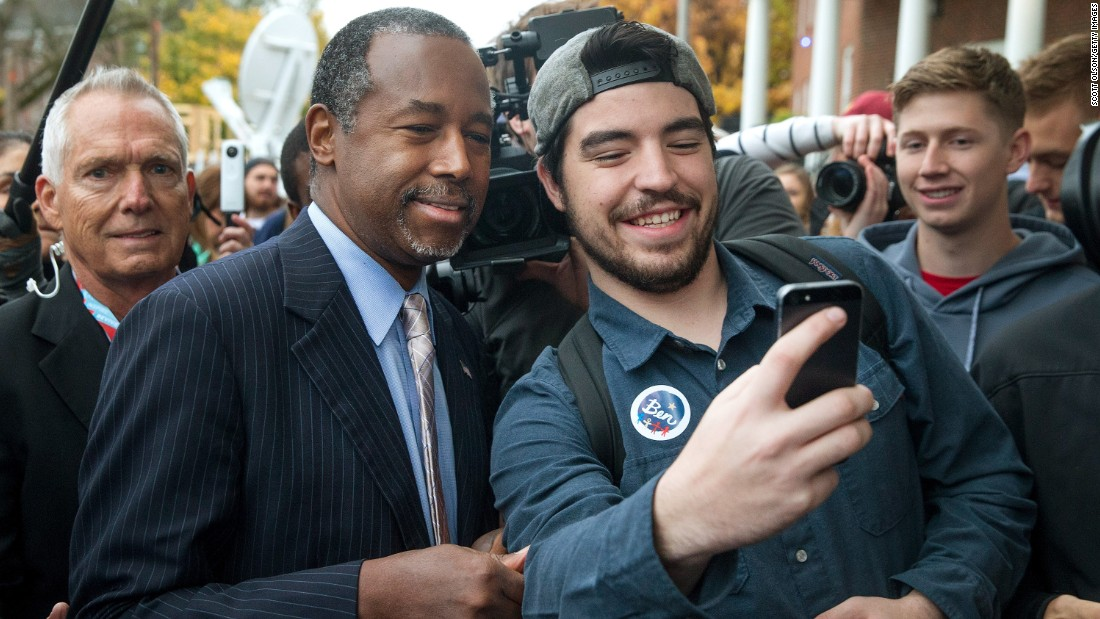 Republican presidential candidate Ben Carson, left, take a selfie outside the Alpha Gamma Rho house during a campaign stop at Iowa State University on Saturday, October 24.