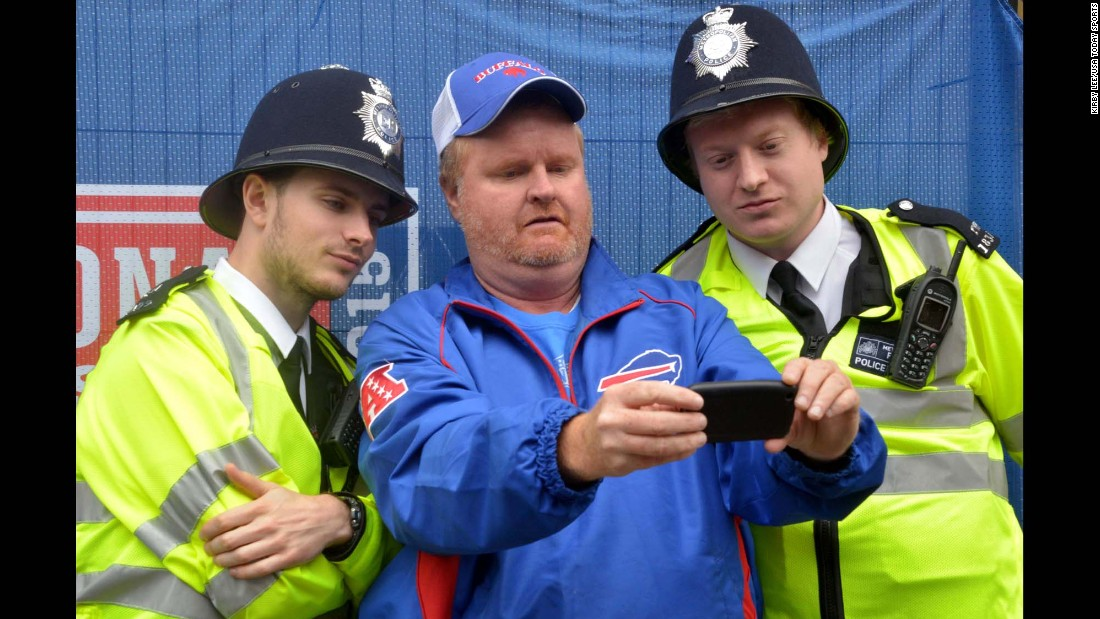 A Buffalo Bills fan poses for a selfie with Metropolitan Police in London on Saturday, October 24, before the International Series NFL game between the Bills and the Jacksonville Jaguars.