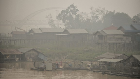 Residents by the Kahayan riverbanks go about their daily lives in haze-hit Palangkaraya on October 25.