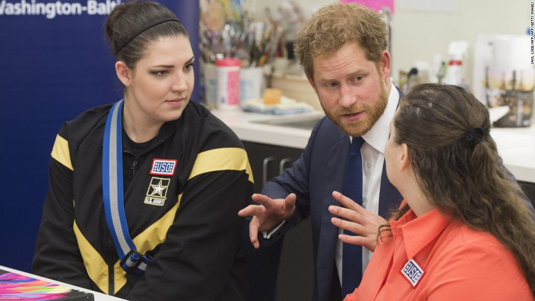 Prince Harry visits with wounded U.S. service members as he looks at their artwork during a tour of the center on October 28.