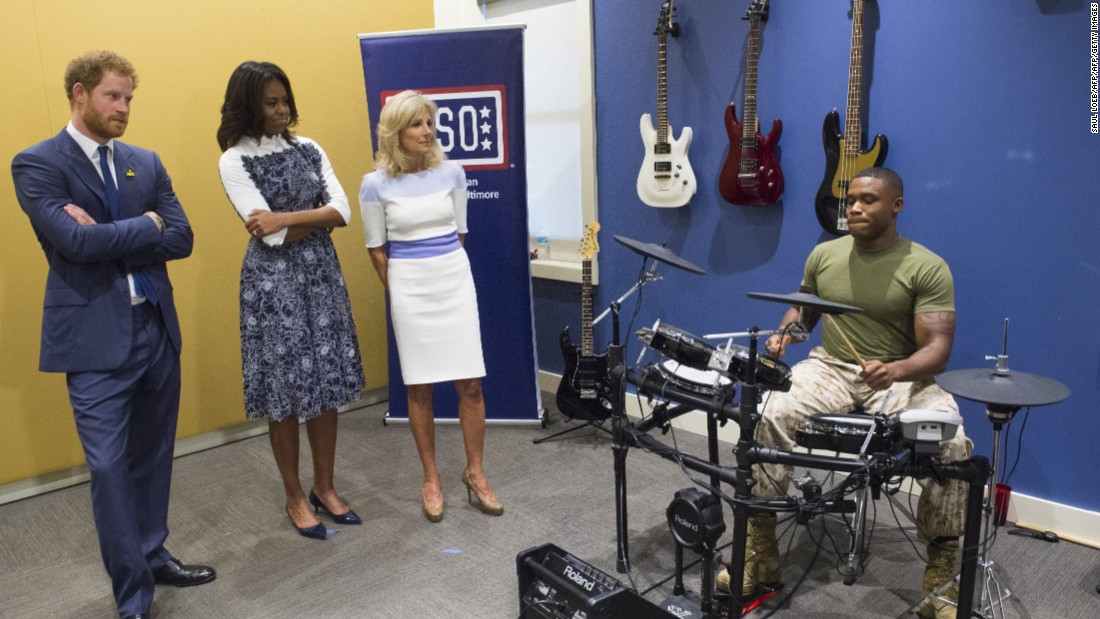 Britain's Prince Harry, U.S. first lady Michelle Obama and Dr. Jill Biden, wife of the vice president, listen to Marine Sgt. Roderic Liggens perform on the drums at the USO Warrior and Family Center at Fort Belvoir, Virginia, on Wednesday, October 28.