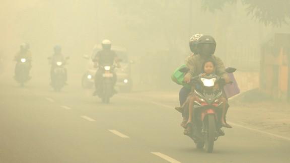 Motorists ride through thick haze choking the city of Palangkaraya, Indonesia, on October 27, 2015.