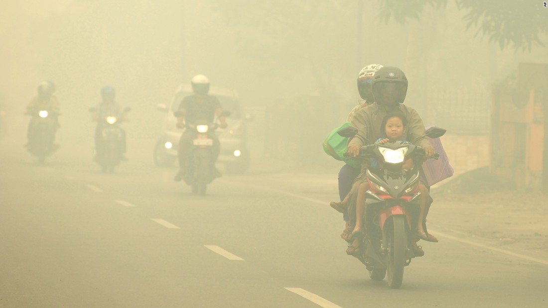 Motorists ride through thick haze choking the city of Palangkaraya, Indonesia, on October 27, 2015.