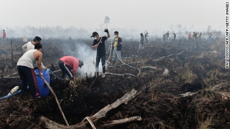 TO GO WITH Indonesia-environment-pollution,FOCUS by Dessy Sagita  This photo taken on October 27, 2015 shows volunteers extinguishing a peatland fire in the outskirts of Palangkaraya, a city of 240,000 in Indonesia's central Kalimantan where respiratory illnesses have soared as the smog has worsened in recent weeks. Desperate civilians at the epicentre of Indonesia's haze crisis are taking the fight into the own hands, using whatever meager resources they have to confront the fires ravaging their communities as they tire of waiting for the government to take action.    AFP PHOTO / Bay ISMOYO        (Photo credit should read BAY ISMOYO/AFP/Getty Images)