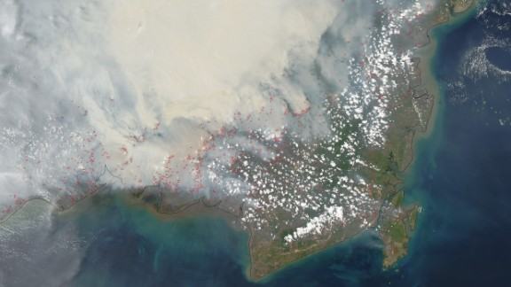 NASA's satellite captured this image of heavy smoke blanketing Borneo on October 19, 2015. The red outlines indicate areas where unusually warm surface temperatures associated with peat fires are detected.