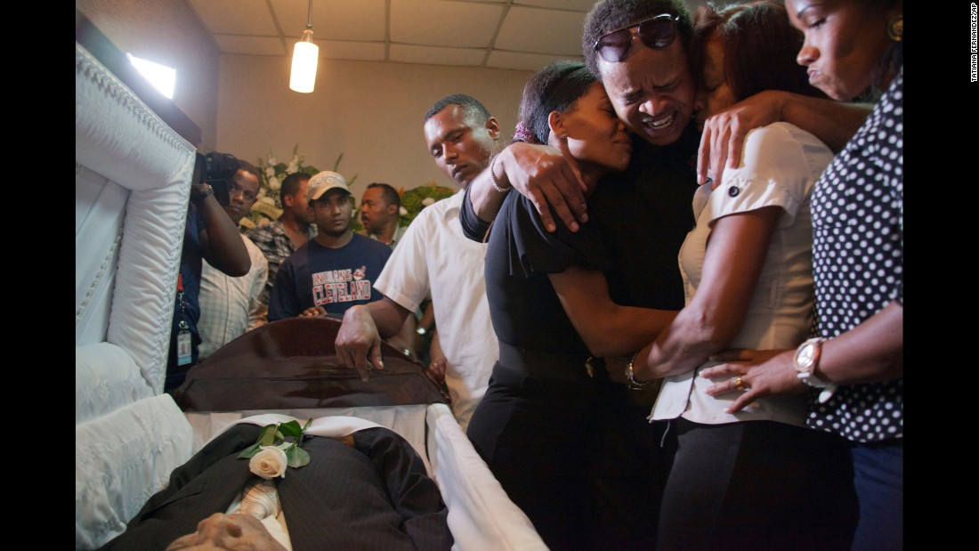 "Kansas City Royals player Edinson Volquez, third from right, embraces his sister Wendy Volquez, left, and mother Ana Ramirez as they stand next to the body of his father during the wake at a funeral home in Santo Domingo, Dominican Republic, on Wednesday, October 28. Volquez played Game 1 of the <a href=""http://www.cnn.com/2015/10/28/us/royals-pitcher-edinson-volquez-father-death/"" target=""_blank"">World Series on Tuesday night</a>, just hours after his father died of heart failure in the Dominican Republic."