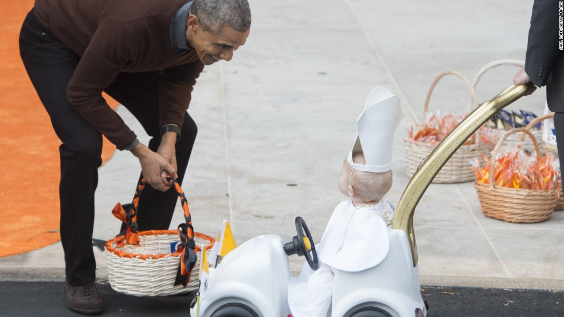 "President Obama greets a young child dressed as the Pope and riding in a ""Popemobile"" as he hands out treats to children trick-or-treating at the White House on October 30."