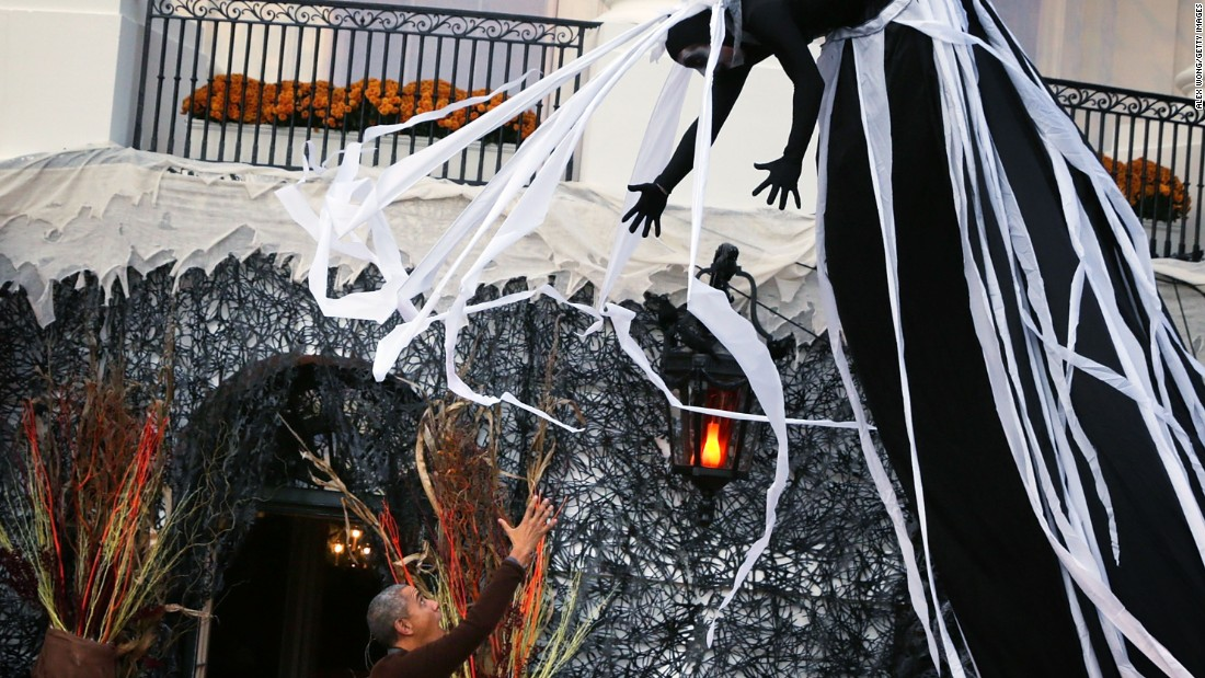 A performer is suspended above President Obama (left) during a Halloween event at the South Lawn of the White House on October 30.