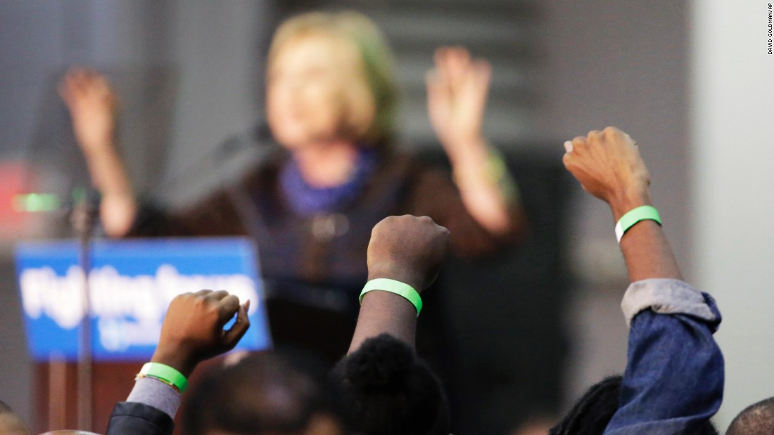 Protesters raise their arms while interrupting Democratic presidential candidate Hillary Rodham Clinton as she speaks during a campaign event at Clark Atlanta University in Atlanta, Friday, Oct. 30.
