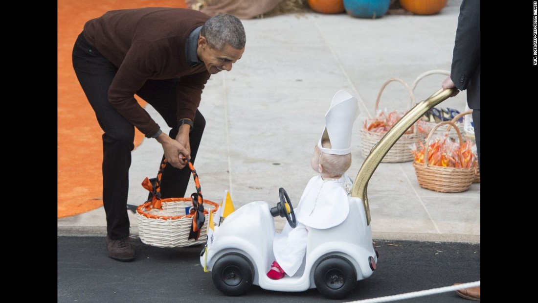 "President Barack Obama greets a young child dressed as the Pope and riding in a ""Popemobile"" as he hands out treats to children trick-or-treating for Halloween on the South Lawn of the White House on October 30."