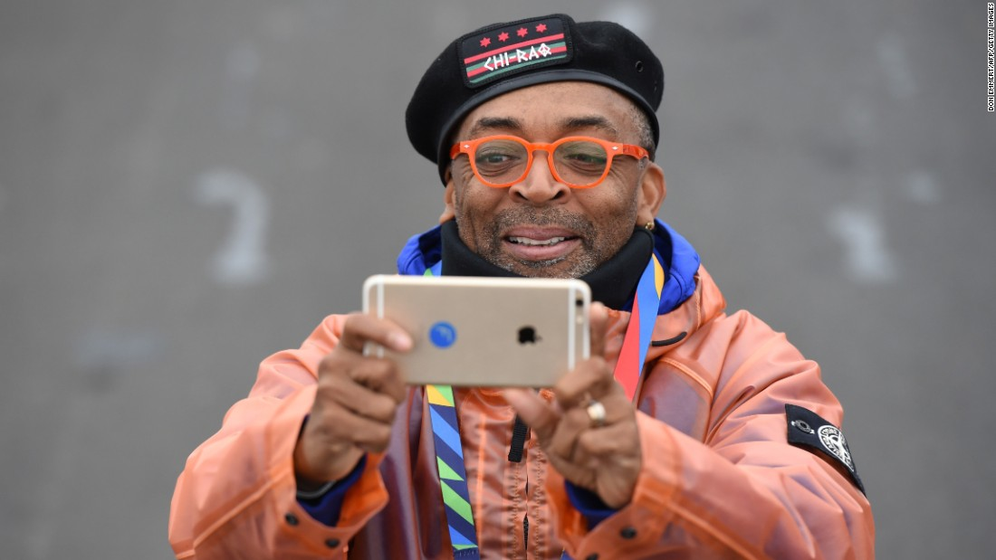 Movie director Spike Lee takes photos of the elite runners as they pass.